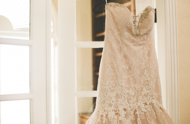 Lace dress hanging in doorway - Photo by Vanessa Lain Photography