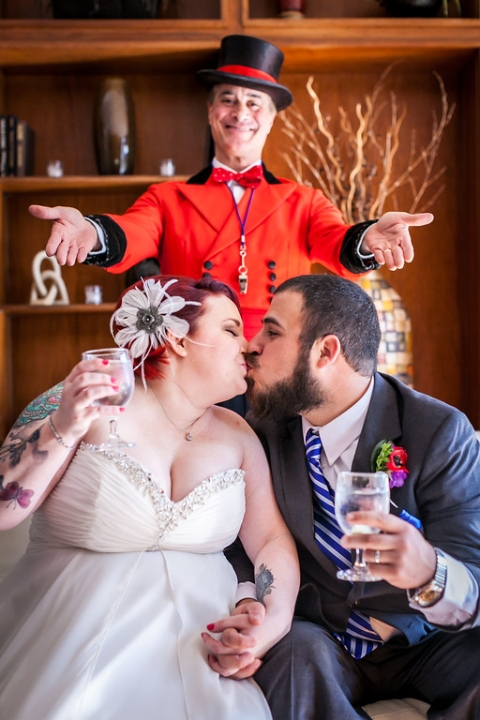 Bride and groom kissing with ringleader behind them - Photo by Daniel Brennan