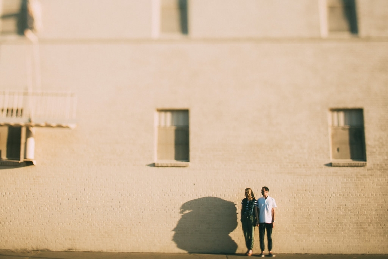 Outdoor engagement photo standing by white brick building at sunset - Photo by Grant Daniels Photography