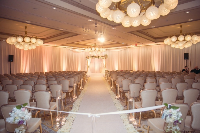Wedding ceremony at the Four Seasons Las Colinas with white draping and floral altar - Photo by TRU Identity Photography + Designs