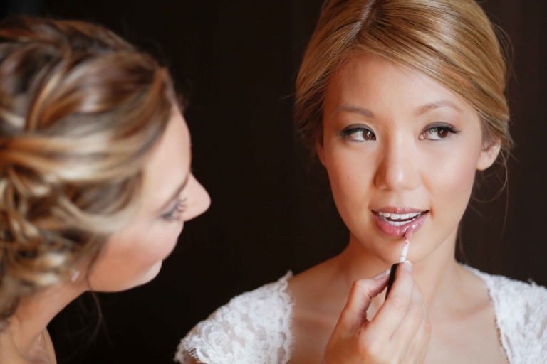 Bride in lace dress having final makeup touches - Photo by Fairy Tale Photography