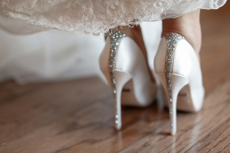 Bride in lace dress with white satin shoes and sparkly details - Photo by Fairy Tale Photography