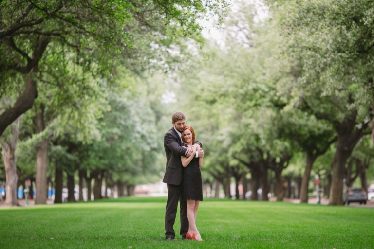 Outdoor engagement pictures in grassy field with trees surrounding - Photo by Evan Godwin Photography