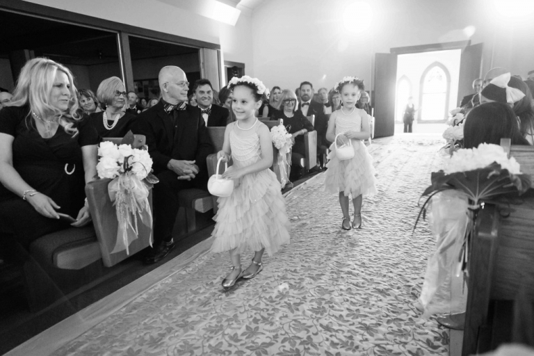 Twin flower girls walking down the wedding ceremony aisle with flower crowns - Photo by Joshua Ayres Photography