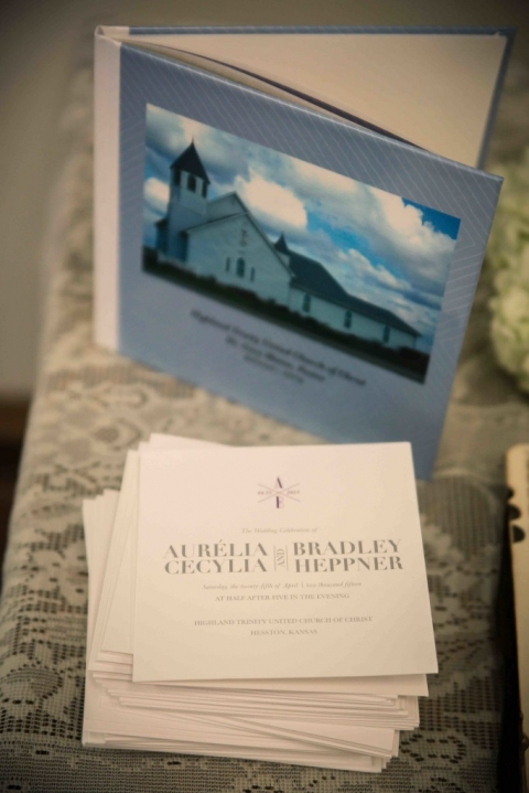 Wedding ceremony folded program on lace table with wedding photo book - Photo by Joshua Ayres Photography