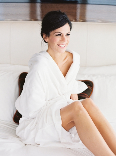 Beautiful bride in white robe sitting on bed before wedding ceremony - Photo by Joshua Aull Photography