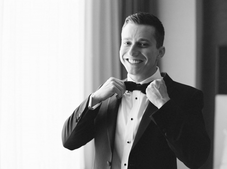 Groom straightening tie on traditional class black tuxedo before wedding ceremony - Photo by Joshua Aull Photography