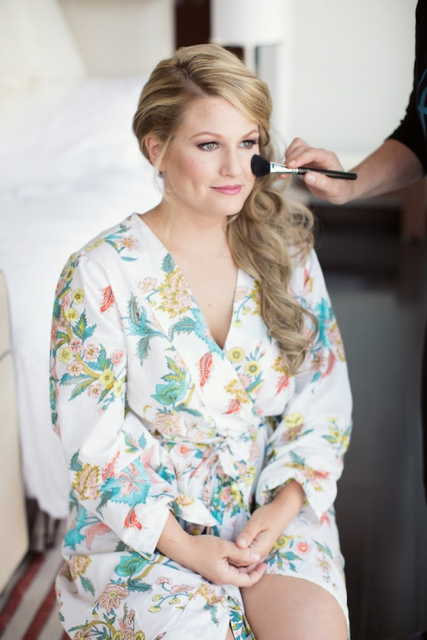 Bride getting having makeup done before wedding ceremony in floral print robe - Photo by Joshua Aull Photography
