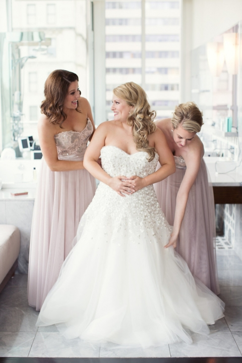 Bridesmaids helping bride put on dress in penthouse suite bathroom of historic Dallas hotel - Photo by Joshua Aull Photography