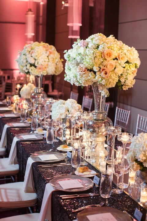 Formal wedding head table with silver Chiavari chairs, silver napkins, BBJ chargers, custom black sequin linen and different sized floral arrangements - Photo by Joshua Aull Photography