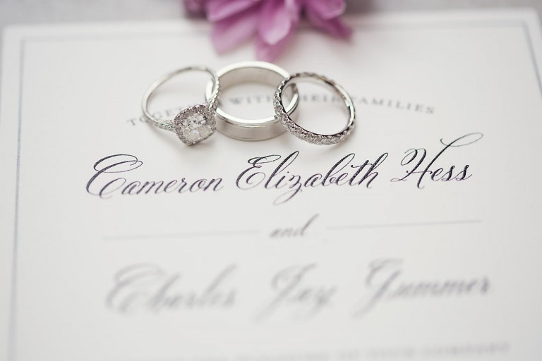 Wedding rings on top of traditional wedding invitation - Photo by Joshua Aull Photography