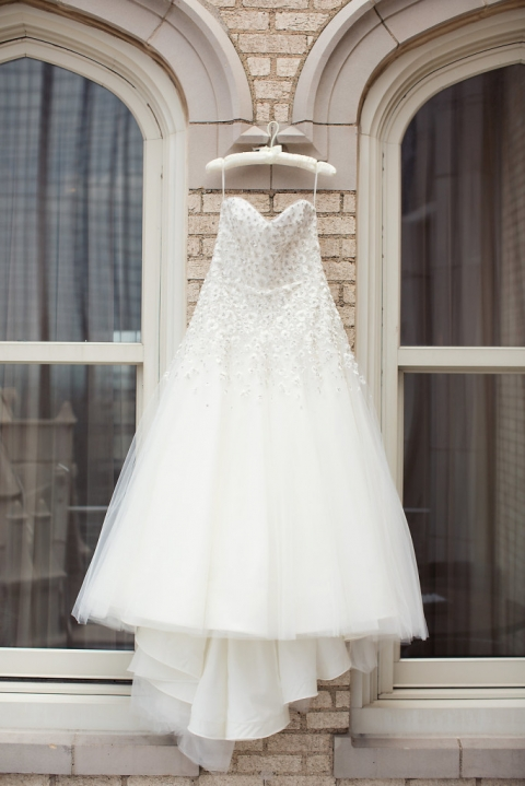 White strapless wedding dress with floral embellishments hanging between two windows outside historic building - Photo by Joshua Aull Photography