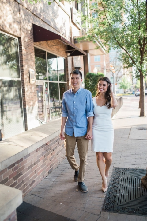 Couple walking in uptown Dallas outdoor engagement photos - Photo by Texas Sweet Photography