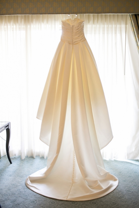 Silk strapless wedding dress with buttons and long train hanging in hotel room window - Photo by Jenny & Eddie