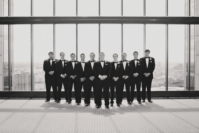 Groom and groomsmen posing in front of large window with Dallas skyline at CityPlace - Photo by Jenny & Eddie