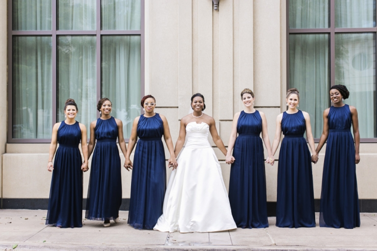 Bride and bridesmaids in long navy dresses holding hands at The Ritz-Carlton - Photo by Jenny & Eddie