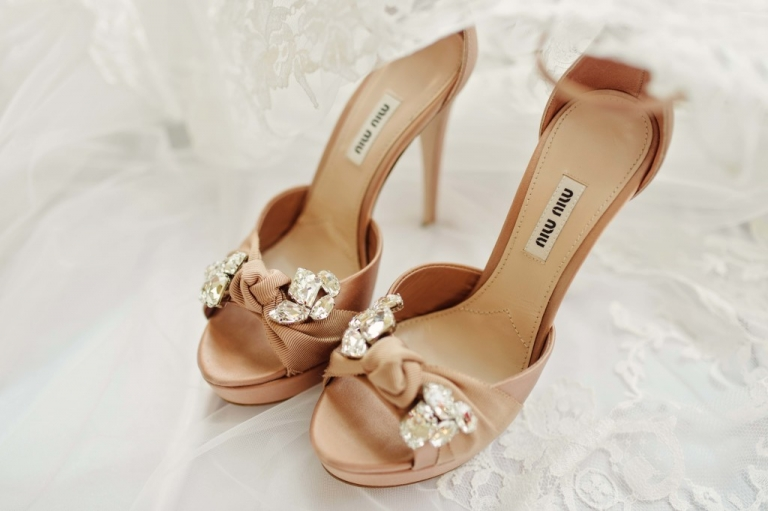 Blush pink wedding shoes with crystal pendants sitting on lace veil - Photos by Celina Gomez Photography