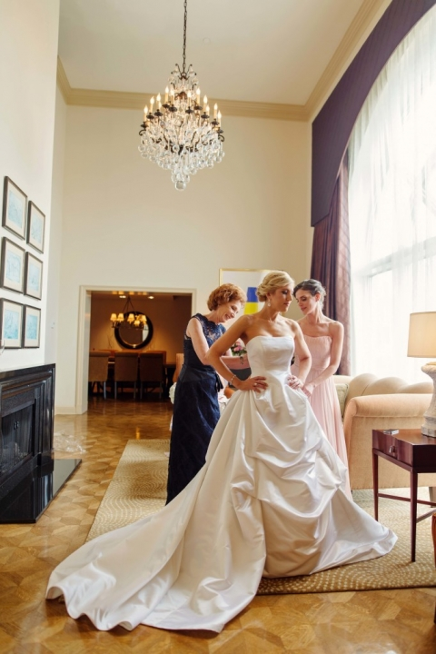 Mother of the bride and maid of honor helping the bride get dressed in penthouse suite at The Crescent Hotel in Dallas, TX - Photos by Celina Gomez Photography