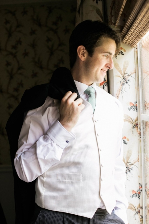 Groom with light green tie posing by window before daytime wedding at the Mansion on Turtle Creek in Dallas, TX - Photo by Lightbox Photography