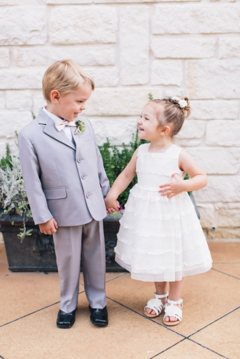 Adorable ring bearer in grey tux with pink bow tie and flower girl in white dress with floral pony tail holding hands before summer wedding ceremony at Ashton Gardens - Photo by Loft Photography