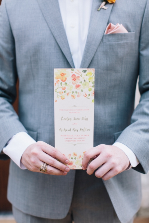 Groomsmen in grey tux with pink pocket square holding floral summer wedding ceremony program - Photo by Loft Photography