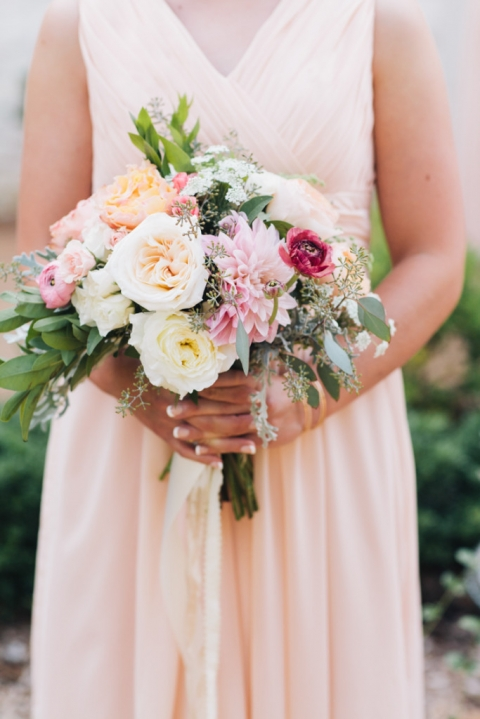 Bridesmaid in soft pink v neck long bridesmaids dress with colorful and lush bridesmaid bouquet for summer wedding - Photo by Loft Photography