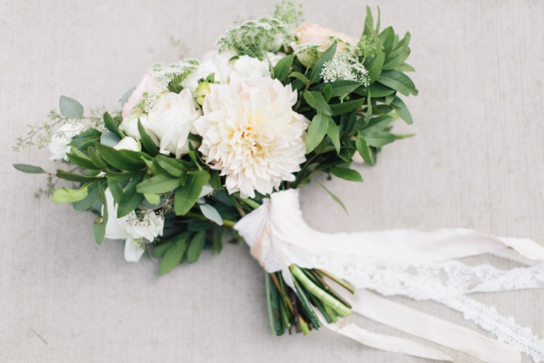 Lush summer brides bouquet with lots of greenery and soft white flowers with ribbon and lace on stems - Photo by Loft Photography