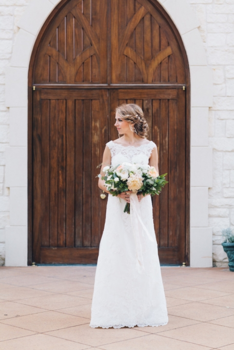Bride in lace off the shoulder wedding dress standing in front of large wooden cathedral doors at Ashton Gardens - Photo by Loft Photography