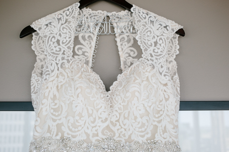 White lace wedding dress hanging on personalized wire last name black hanger with wedding dress with beaded belt - Photo by F8 Studio