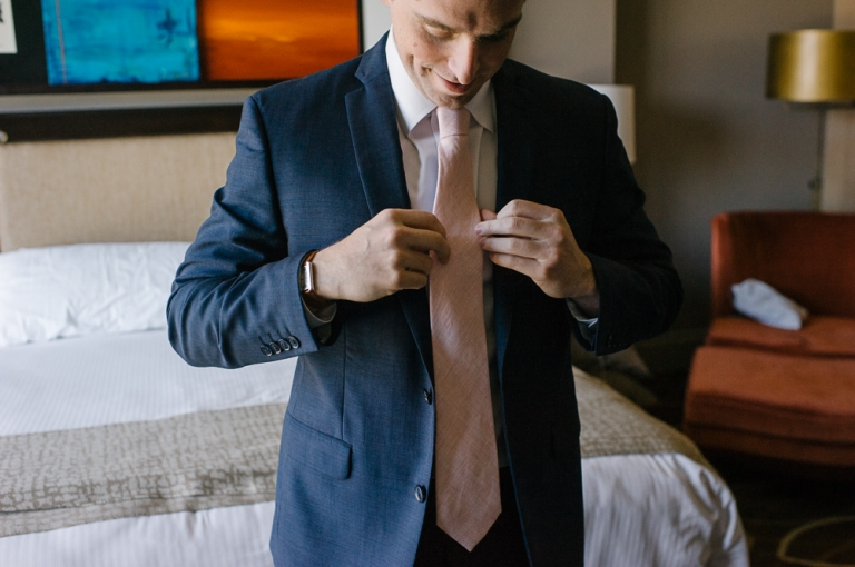 Groom putting on navy suit with pink tie for wedding day - Photo by F8 Studio