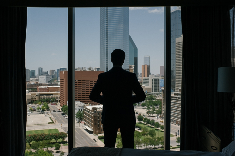 Groom standing in window at the Omni in Downtown Dallas on wedding day - Photo by F8 Studio