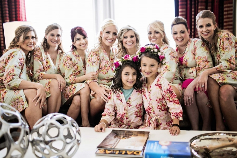 Bride and bridesmaids in short floral robes with flower girls in flower crowns and mini floral robes getting ready for summer wedding in Dallas, TX - Photo by Jenny & Eddie