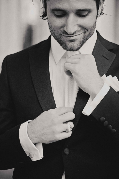 Groom in formal black tuxedo straightening white tie before summer wedding ceremony at The Joule in Dallas, TX - Photo by Jenny & Eddie