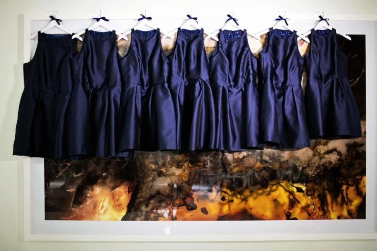 Navy blue bridesmaids dresses hanging on white hanger with bridesmaids names written on navy wire - Photo by Jenny & Eddie