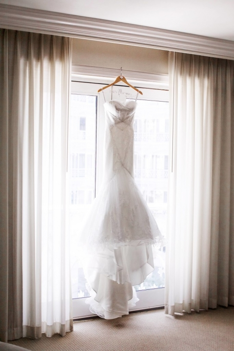 Brides strapless wedding dress hanging on custom last name hanger in tall window in hotel in Dallas, TX for summer wedding - Photo by Jenny & Eddie copy