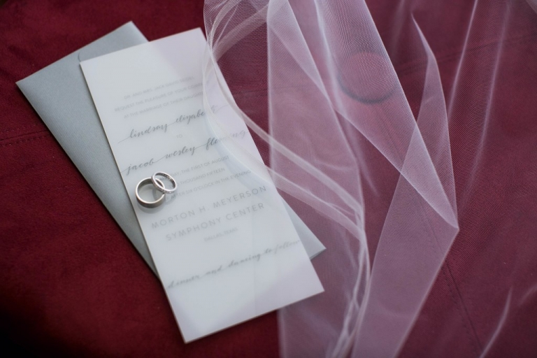Wedding rings on top of rectangular vellum wedding invitation for modern summer wedding - Photos by Jenny & Eddie