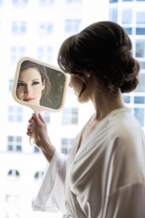 Bride looking in handheld mirror while after getting hair and makeup done before summer wedding in Dallas, TX - Photos by Jenny & Eddie