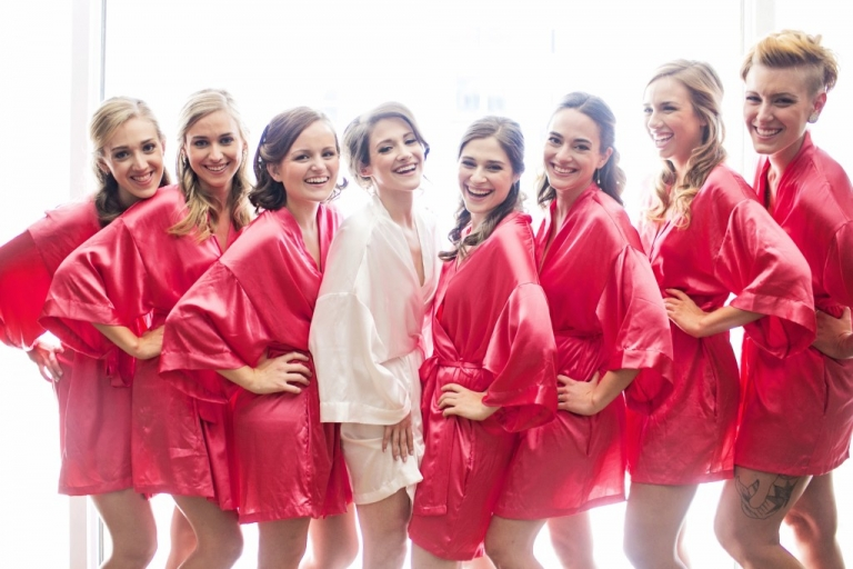 Bride in white robe and bridesmaids in pink robes bridesmaids gift idea before summer wedding in Dallas, TX - Photos by Jenny & Eddie