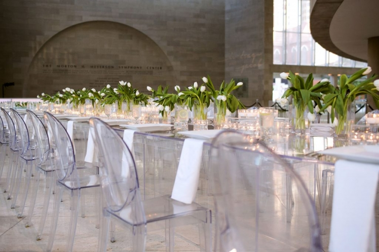 Modern wedding head table with lucite tables and chairs and white tulips as floral centerpieces - Photos by Jenny & Eddie