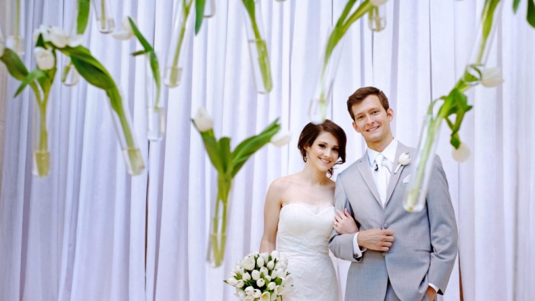 Summer wedding at Meyerson Symphony Center in Dallas, TX couple posing behind wall of suspended white tulips - Photos by Jenny & Eddie