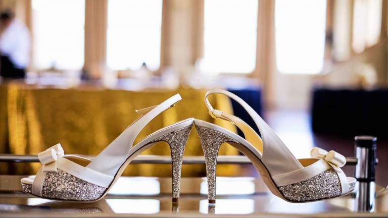 White and silver sparkle Kate Spade wedding day shoes with white satin bow - Photos by Jenny & Eddie
