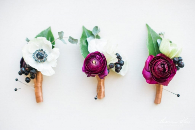 Groom and groomsmen boutonnieres with deep purple ranunculus wraped in gold ribbon with greenery for fall wedding - Photos by Shannon Skloss Photography