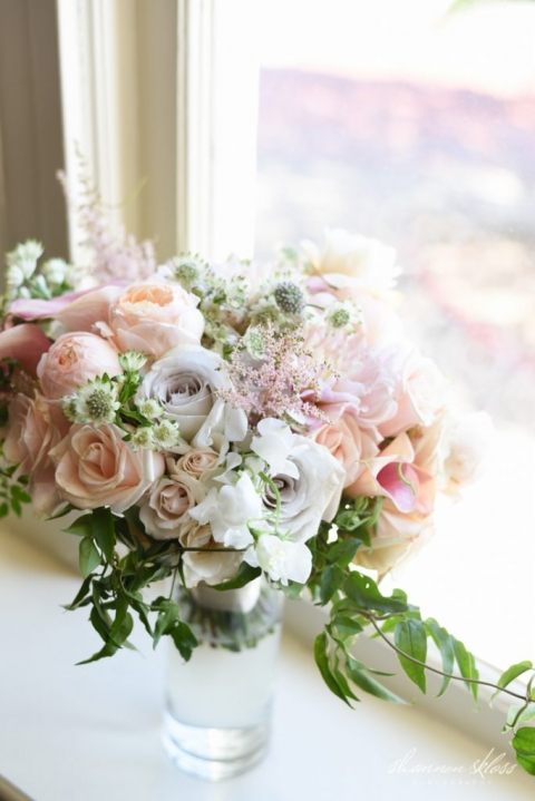 Lush bridal bouquet with pink, peach, ivory, and white flowers with greenery - Photos by Shannon Skloss Photography