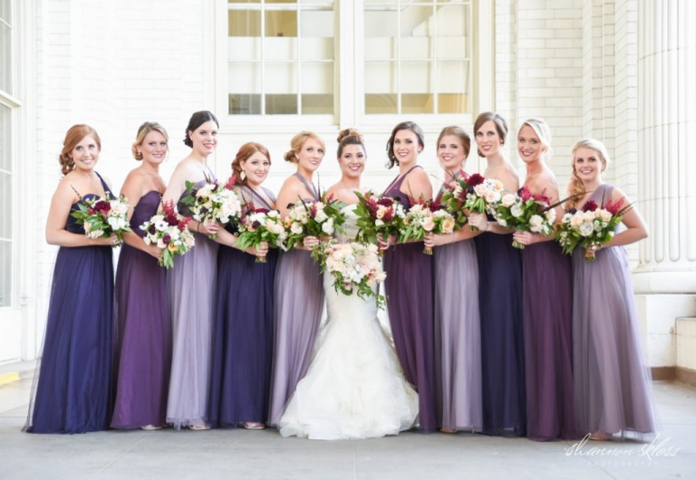 Bride and bridesmaids with lush fall wedding bouquets bridesmaids in mismatched purple colored long dresses - Photos by Shannon Skloss Photography