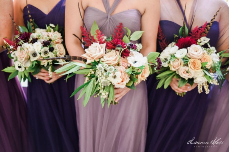 Lush fall bridesmaids bouquets with lots of texture greenery reds pinks and whites flowers bridesmaids in mismatched pruple dresses - Photos by Shannon Skloss Photography