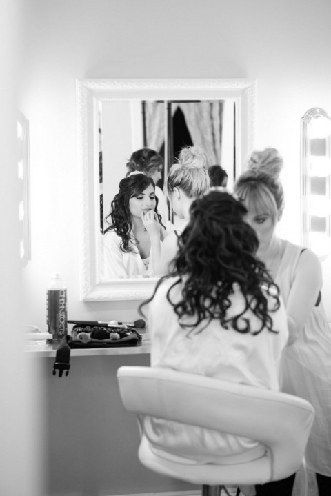 Bride getting ready in white robe for fall wedding at The Milestone - Photos by The Mamones
