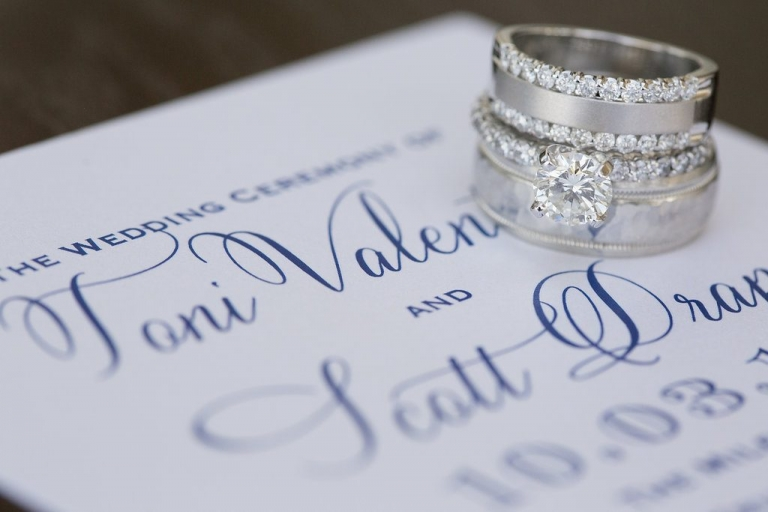 Bride and grooms wedding rings on custom white and navy wedding invitation - Photos by The Mamones
