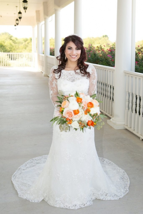 Bride in long sleeved lace wedding dress with white orange and peach colored wedding bouquet for fall wedding at The Milestone - Photos by The Mamones