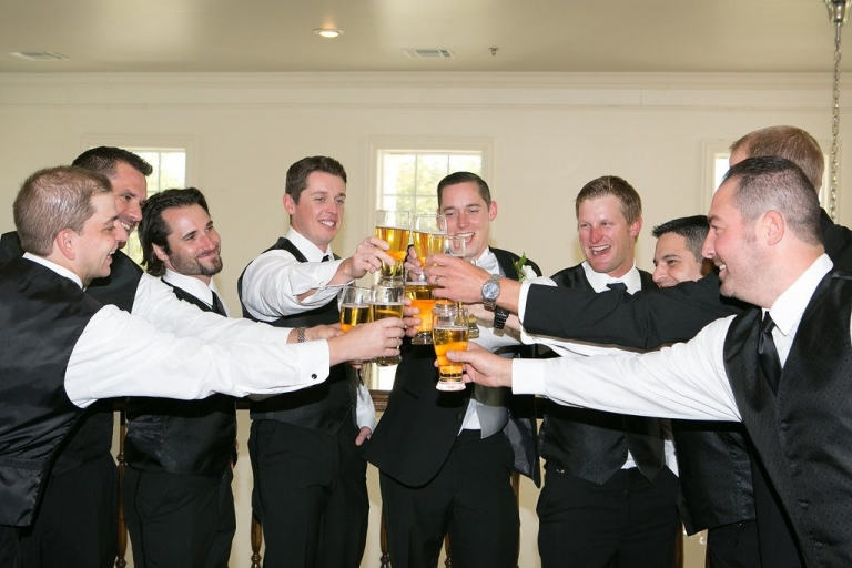 Groom and groomsmen cheers with beers before fall wedding ceremony at The Milestone - Photos by The Mamones