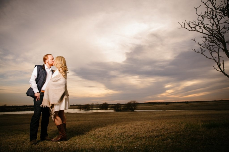 Outdoor engagement photos bride in white dress groom in quilted vest kissing in open field at sunset - Photos by Stephen Karlisch